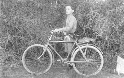 Portrait of an unidentified child with a bicycle