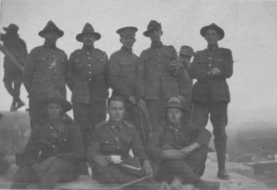 A group of eight men in New Zealand Army uniform standing on top of a pyramid.  Les Grant is on the far right, the other men are unidentified.