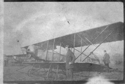 Donald Ernest Harkness standing by a plane