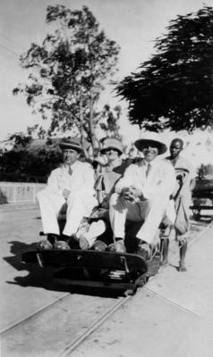 Two unidentified men and one woman on a rail handcar