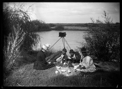 Four people having a picnic by the Tutaekuri River; Duncan, Russell