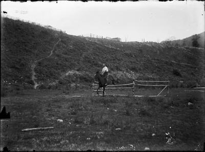 Man on horse jumping over makeshift jump