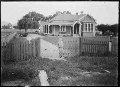 House, with boy at front gate