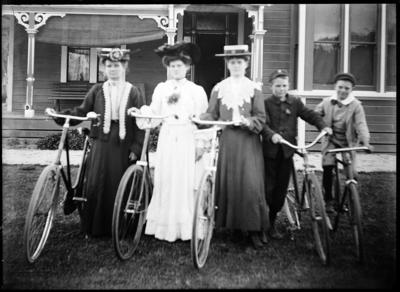 Three women and two boys with bicycles