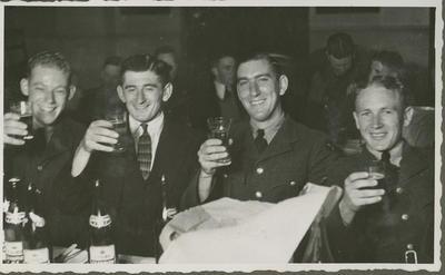 Four men raising their glasses