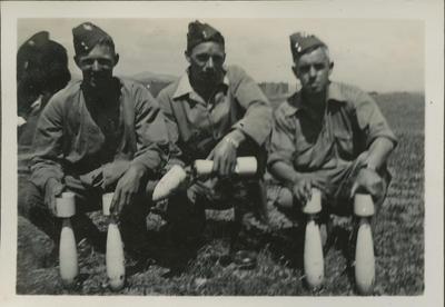 Three RNZAF men with artillery shells