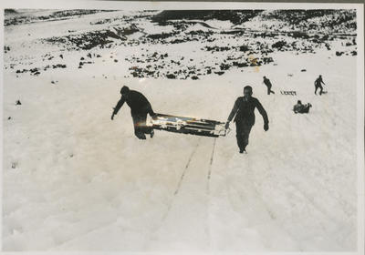 Two men carrying a sled up a snow covered mountain slope