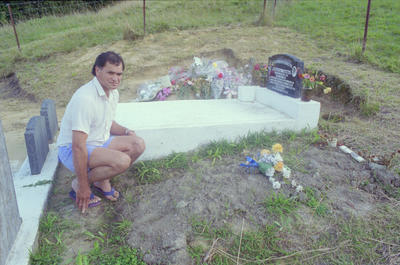 George Tawhai at the two flower-covered plots where his daughter and father lie buried