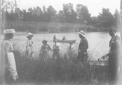 Group on riverbank near bridge