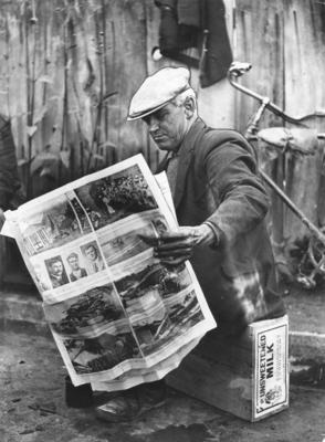 Relief worker reading a copy of the Evening Post