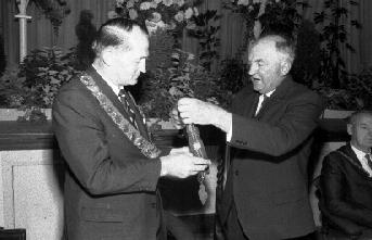As a token of the union of Taradale borough with Napier city, Mr Arthur Miller, Mayor of Taradale, hands his chain of office to the Napier Mayor, Mr Peter Tait