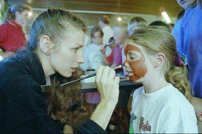 Philippa Loan, 8, having her face painted by librarian Nicoleta Paxie