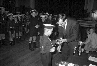 Reverend James presents the Munro Cup and miniature to Taradale Boys' Brigade member Ross Ennis