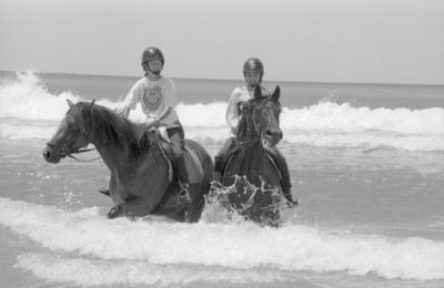Amy Wilder from Waipukurau and Margot Lowry of Hastings riding horses in the surf